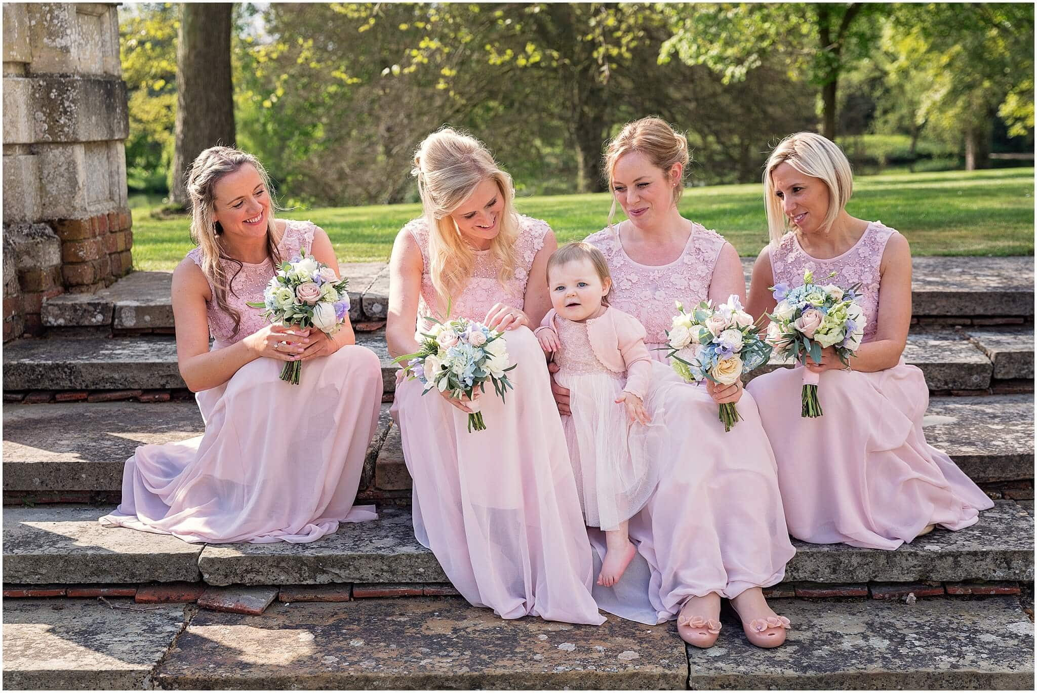 Soft pink bridesmaid dresses and spring flowers at Longstowe Hall