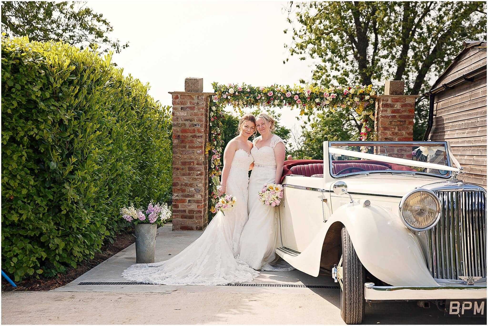 Two brides and wedding car