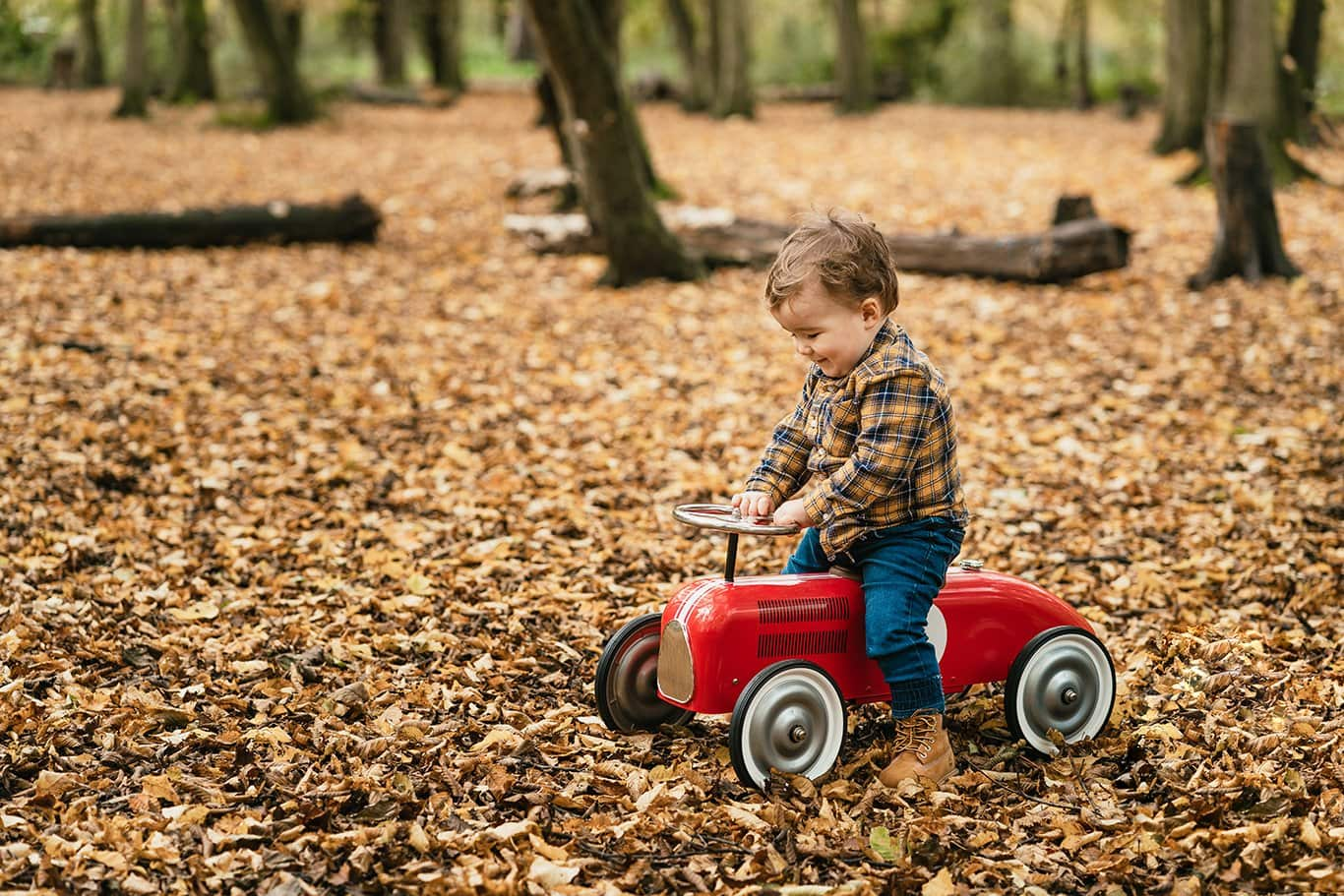 Little boy on a car in the woods