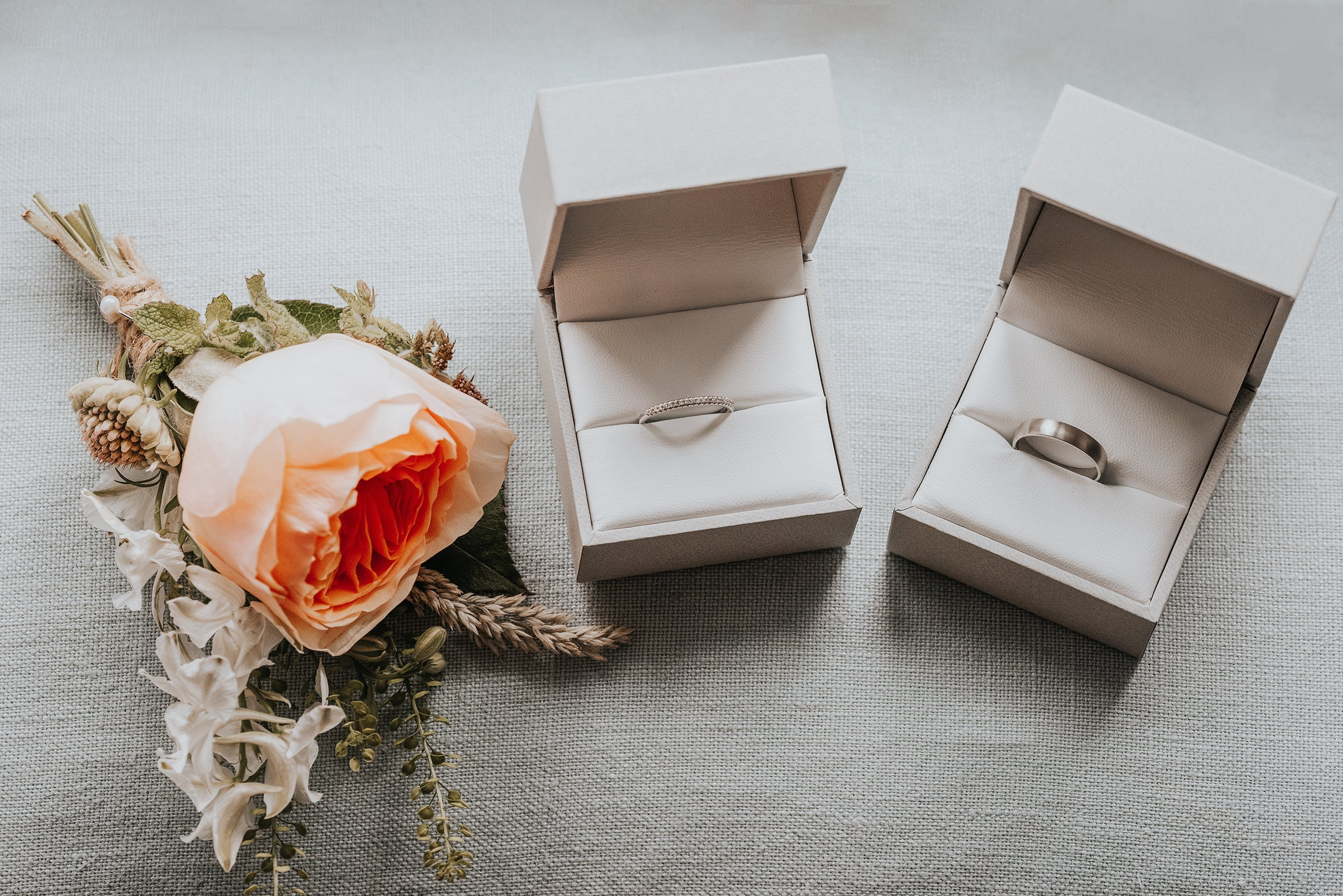 Wedding rings in boxes and button hole flower