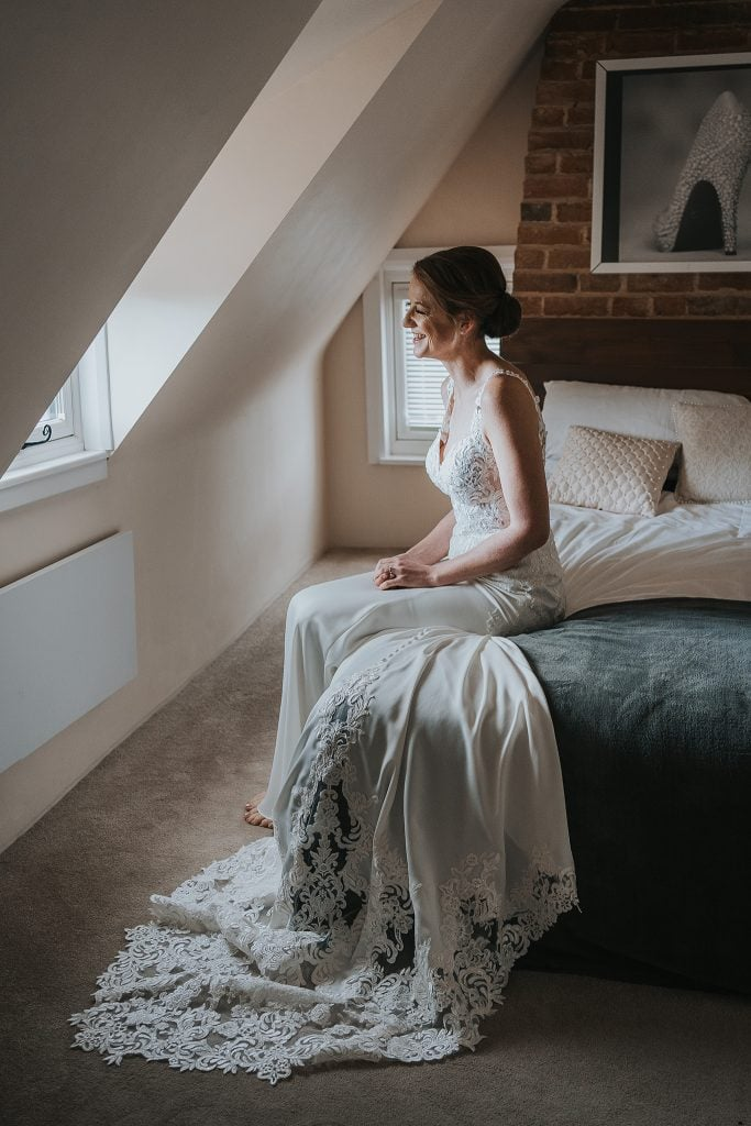 Bride sitting on a bed at Sheene Mill