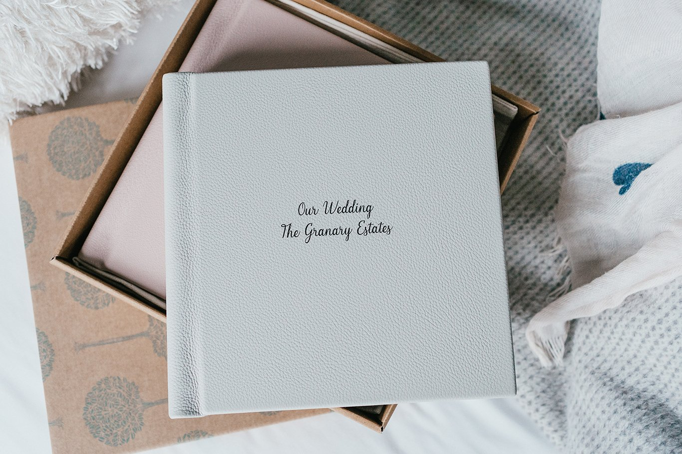 Wedding album in a box on a bed
